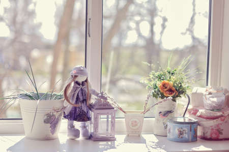 against the window of flowers in pots on the windowsill is a doll photo