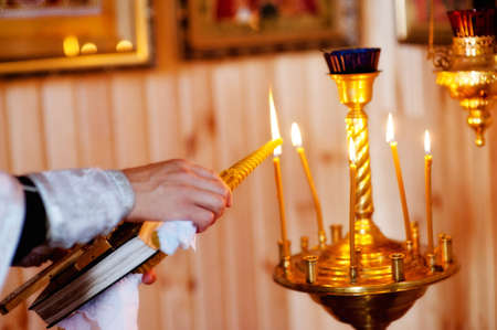 man hand lighting candles in a church photo