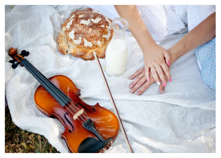 lying on a white blanket and violin couple s hands with rings photo