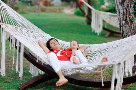 vacationing: outdoors in a white hammock resting father and son in red shirts
