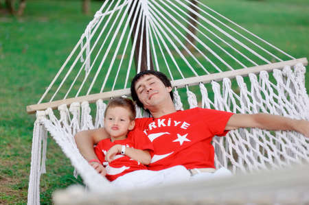 outdoors in a white hammock resting father and son in red shirts photo