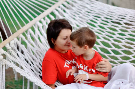 outdoors in a white hammock relax the mother and son in kasnyh shirts photo
