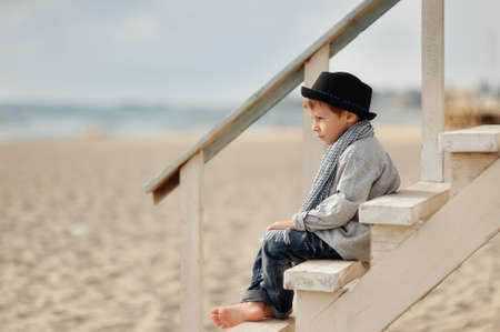 Stylish boy in a hat sitting on a wooden bridge on the background of the sea photo