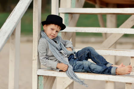 Trendy boy posing lying on the stairs in jeans and a hat barefoot photo