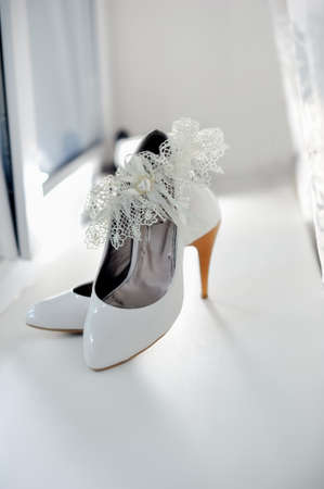 White shoes of the bride on a white background photo