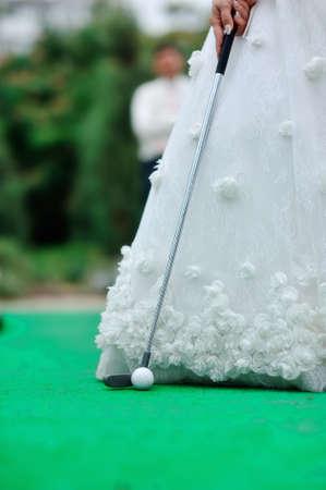 on the green grass beautiful white bridal dress golfing photo