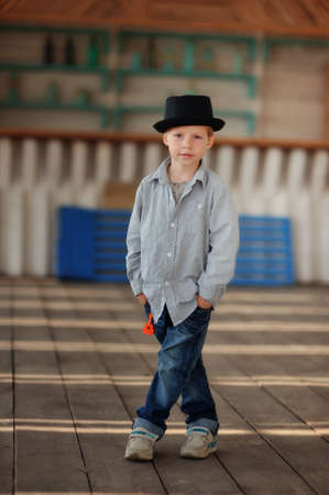 beautiful child in a black hat and jeans posing on a wooden floor