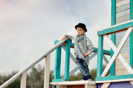 on the wooden stairs is an emotional boy in a black hat with a scarf Stock Photo - 15440476