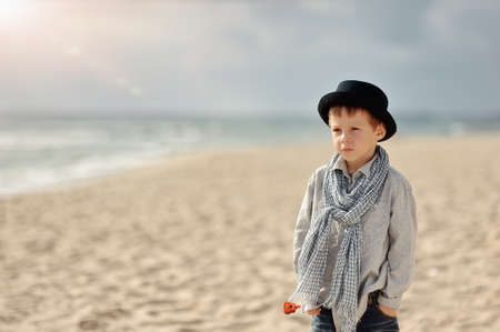 on the shore is thoughtful boy in a black hat with a scarf photo