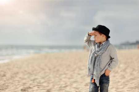 emotional boy in black hat and jeans posing on the beach
