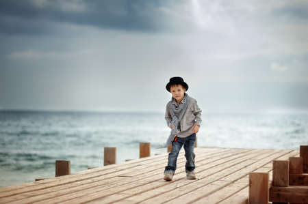 Stylish boy in a hat standing on a wooden bridge on the background of the sea Stock Photo - 15483201