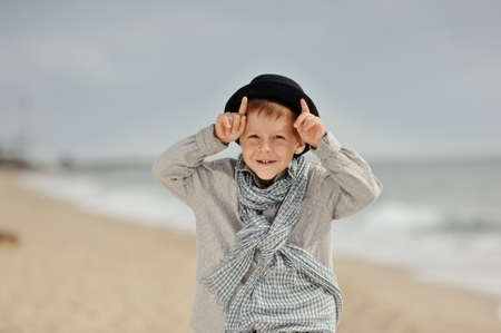 emotional boy in black hat and jeans posing on the beach photo