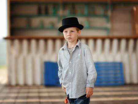 beautiful child in a black hat and jeans posing on a wooden floor Stock Photo - 15451870