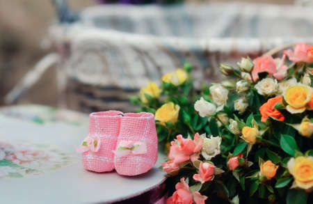 Baby booties with flowers sitting on a white background
