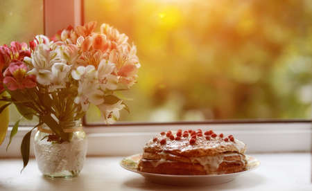 against the background of the window is a cake with berries and a bouquet of flowers near photo