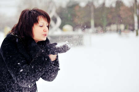 outdoors in winter woman in a black fur coat playing with snow photo