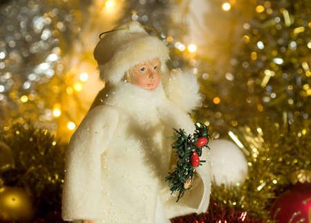 in the golden tinsel toy boy in a white suit with a tree in his hand Stock Photo - 15959370