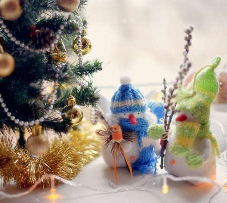 toy angel a snowman in a blue cap under a fir-tree Stock Photo - 15941981