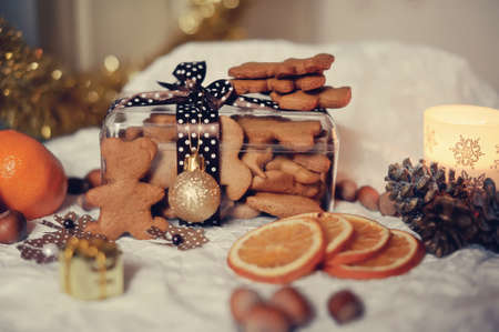 On a white table are dried orange segments and a box of biscuits, nuts and cones photo