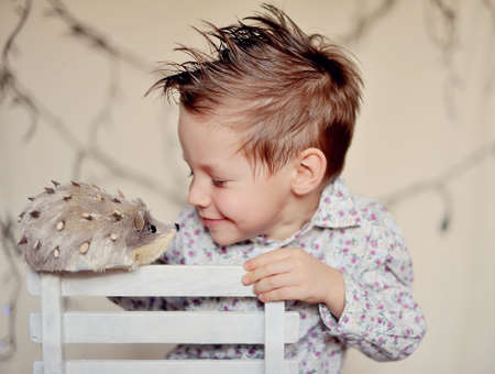 The child with a hedgehog on a chair under a garland photo