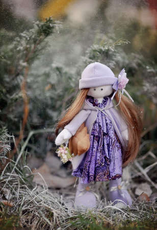 the grass is handmade doll in a purple dress and hat photo