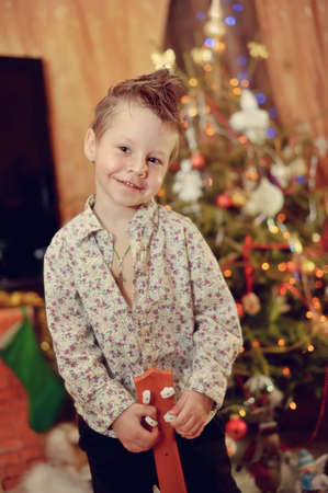 Christmas tree node boy with stylish hairstyle posing with a guita photo