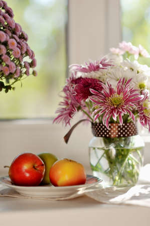 on a white plate ripe apples and bright bouquet of autumn flowers photo