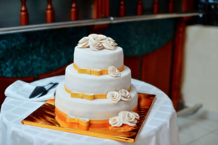 high white wedding cake with beautiful flowers on a golden pedestal