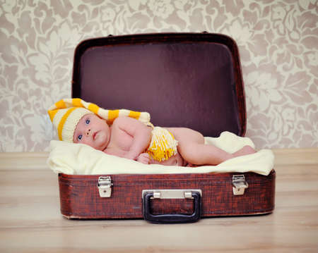 naked baby in a warm hat is in the suitcase photo