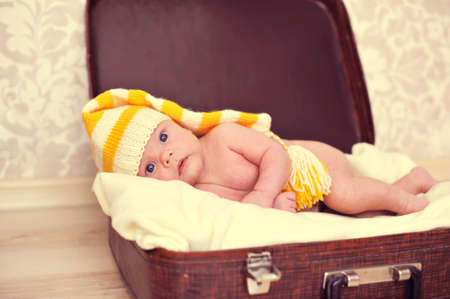 naked baby in a warm hat is in the suitcase Stock Photo - 16164980