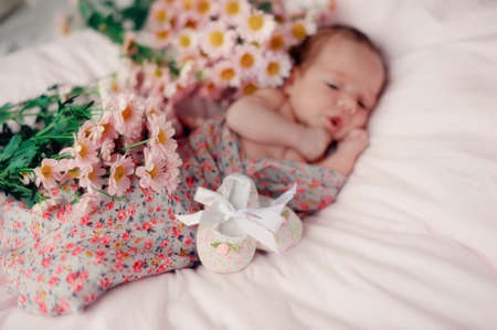 Cute baby lying on the bed and around the autumn flowers photo