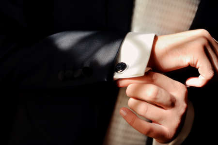 cufflink: Close-up of a man in a tux fixing his cufflink  Stock Photo