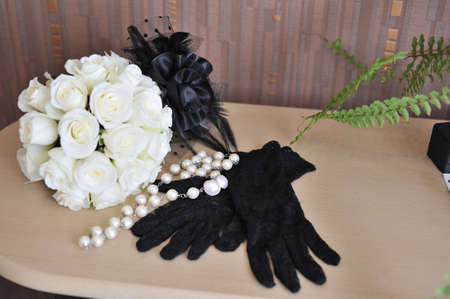 composition-white bouquet of roses and black gloves photo