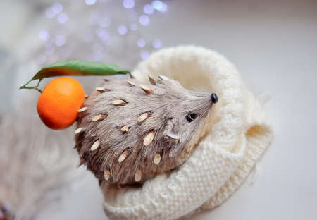 against the background of lights toy hedgehog with tangerine on a thorn Stock Photo - 16715767