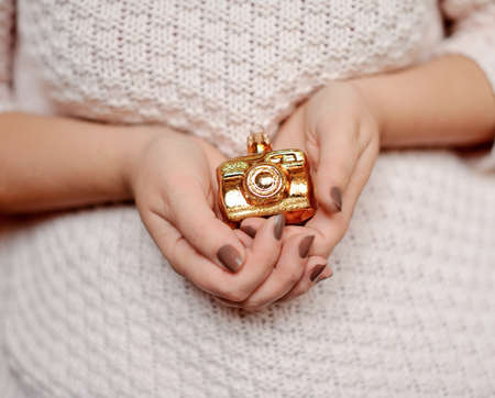 christmas manicure: woman s hands with manicure holding a Christmas toy golden