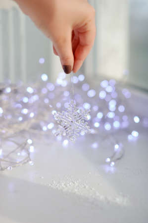 amid garlands of lights female hand holds a toy snowflake Stock Photo - 16715910