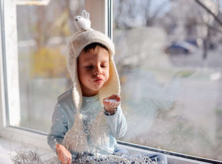 winter boy sitting by the window in a white knitted cap Stock fotó