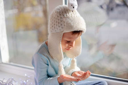 winter boy sitting by the window in a white knitted cap photo