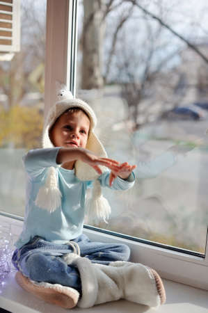 winter boy sitting by the window in a white knitted cap Standard-Bild