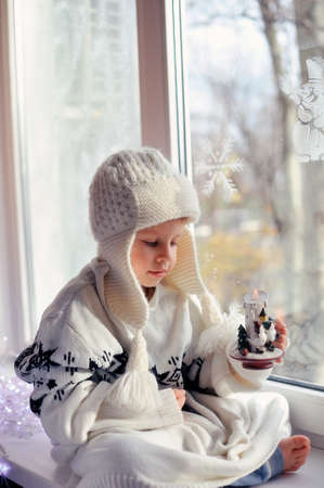 winter boy sitting by the window in a white knitted cap Stock Photo - 16715890