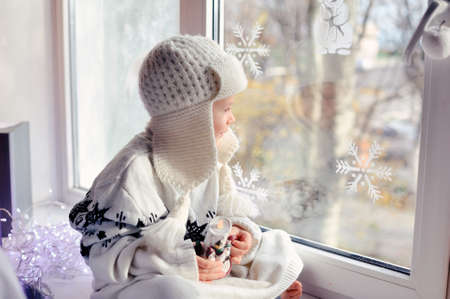 winter boy sitting by the window in a white knitted cap Stock Photo