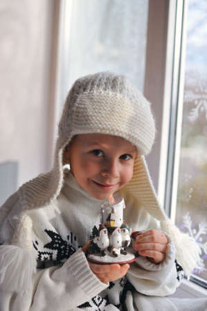 winter boy sitting by the window in a white knitted cap Stock Photo - 16715882