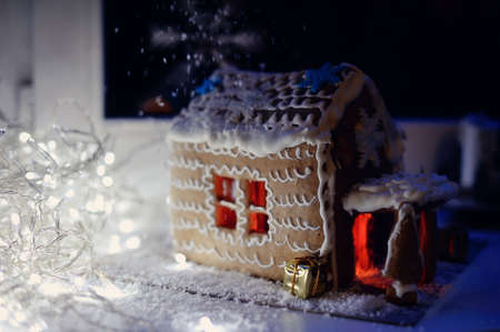 Christmas cake, a small house with snowflakes, and fire in the snow Stock Photo - 16734427