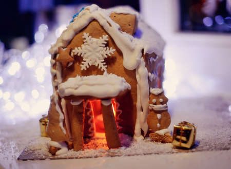 Christmas cake, a small house with snowflakes, and fire in the snow photo