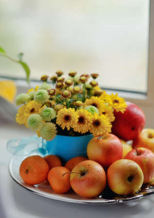 on a white background ripe apples, mandarin bright bouquet of autumn flowers in the window photo