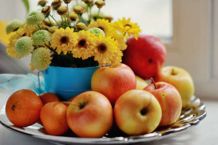 georgina: on a white background ripe apples, mandarin bright bouquet of autumn flowers in the window Stock Photo
