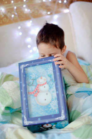 boy woke up in his bed and was a Christmas gift photo