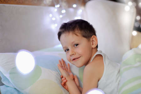 the little boy woke up in a children s cozy bed of lights photo