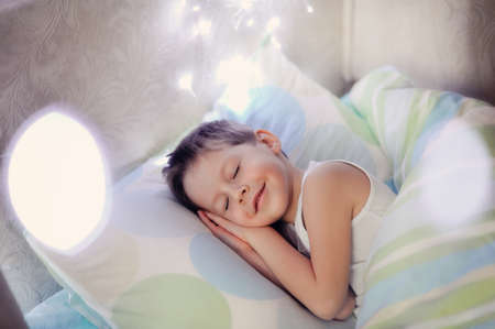 little boy sleeping in a cozy bed child photo
