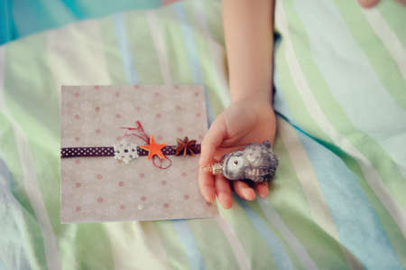 in the child s hand and toy lies next to a beautiful card Stock Photo - 16909125